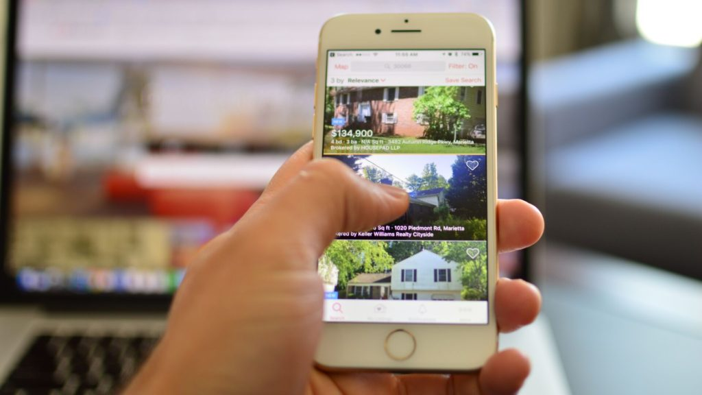Hand scrolling through real estate ads on a smartphone